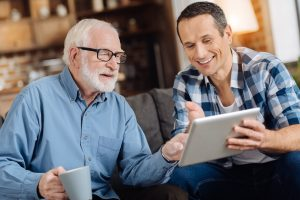 Old father and son with tablet